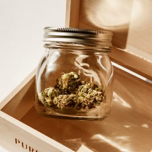 clear mason jar with cannabis inside, sitting in a wooden hinged box
