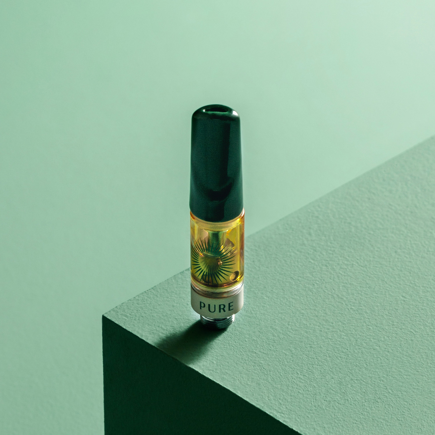 Pure Sunfarms High THC Vape cart sitting upright on the corner of a green table with a green background