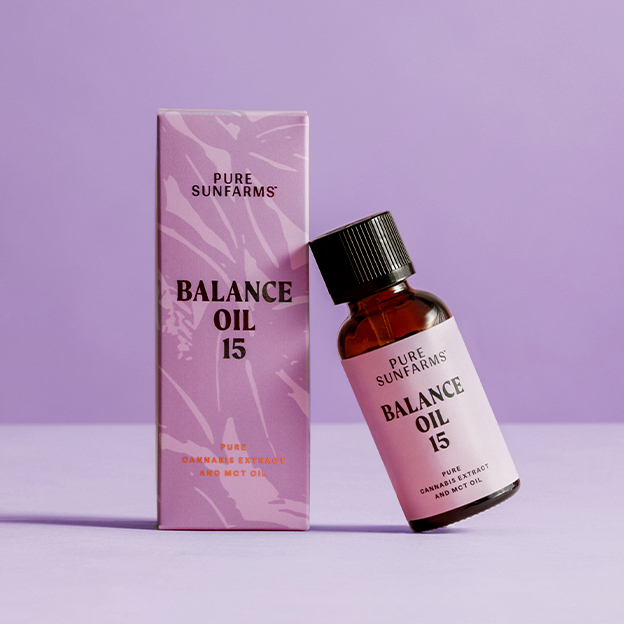 """cbd oil bottle concept packaging leaning on a box that reads """"Balance Oil 15"""" on purple background"""