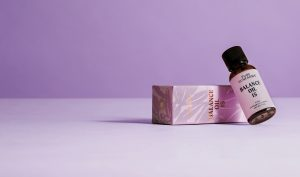 cbd oil bottle concept packaging leaning on a box on purple background